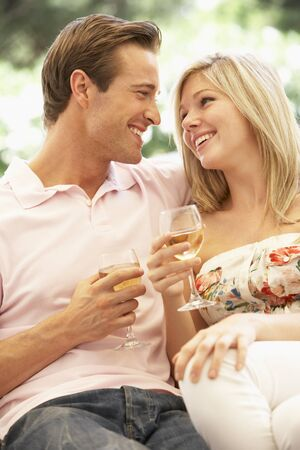 tomando vino: Portrait Of Young Couple Relaxing On Sofa Drinking Wine Together