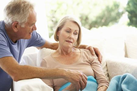 sick person: Husband Comforting Senior Woman Feeling Unwell Resting Under Blanket
