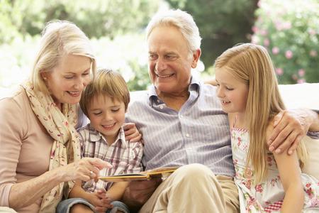 abuelos: Retrato de abuelos a nietos lectura en el sofá Foto de archivo