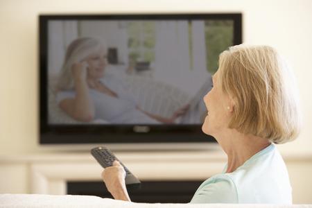 年配の女性が自宅のワイド スクリーンのテレビを見て 写真素材