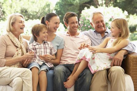 abuelos: Familia de tres generaciones que se sienta en el sofá junto