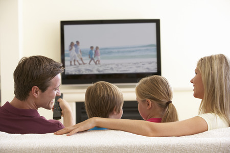 Family Watching Widescreen TV At Home. Stock Photo