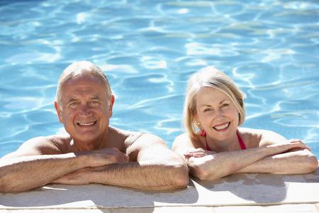 Relaxing ältere Paare, die im Swimmingpool Zusammen Standard-Bild
