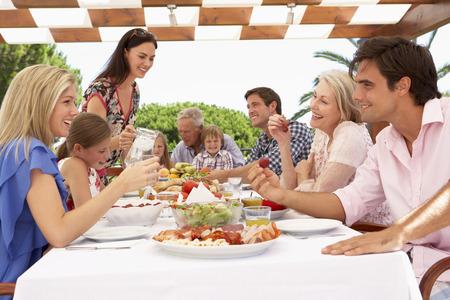 niños platicando: Extended grupo familiar disfruta de la comida al aire libre, junto