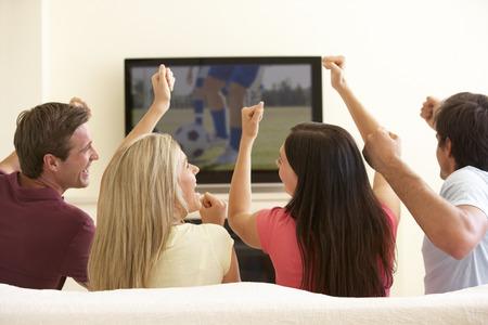 家庭でワイド スクリーン テレビを見ている友人のグループ