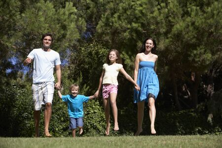 5 year old girl: Young Family Running Through Summer Field