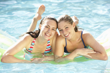 lilo: Portrait Of Two Young Women Relaxing In Swimming Pool