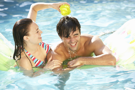 lilo: Portrait Of Young Couple Relaxing In Swimming Pool Stock Photo