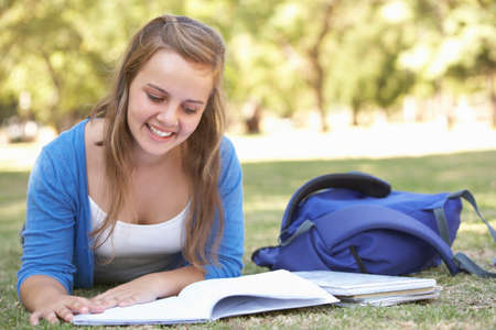 textbook: Female College Student Lying In Park Reading Textbook Stock Photo