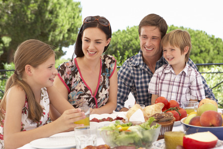 familia comiendo: Familia joven que disfruta de la comida al aire libre Juntos Foto de archivo