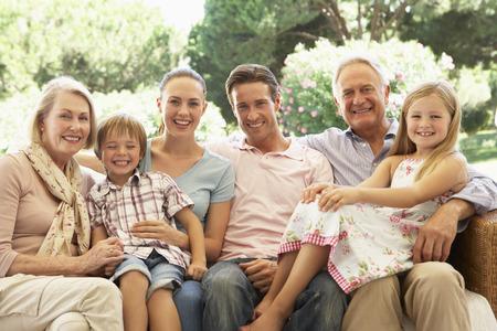 Tři generace rodiny sedí na gauči spolu Reklamní fotografie