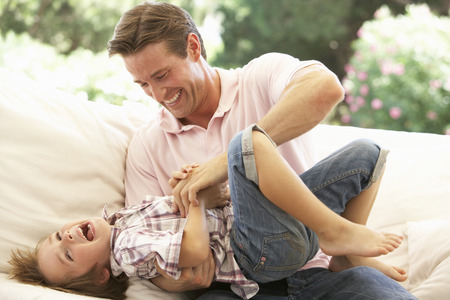 tickling: Father With Son Laughing Together On Sofa