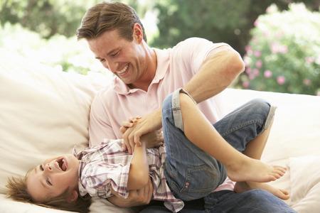 Padre con el hijo de risa junto en el sofá
