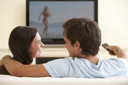 couple home: Couple Watching Widescreen TV At Home