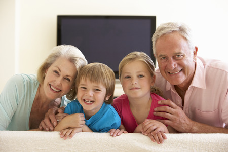 widescreen: Grandparents And Grandchildren Watching Widescreen TV At Home