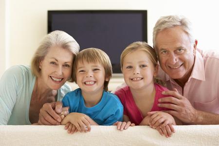 abuelos: Abuelos y nietos que ven la TV de pantalla ancha en el hogar