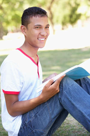 revision book: Teenage Boy Sitting In Park Reading
