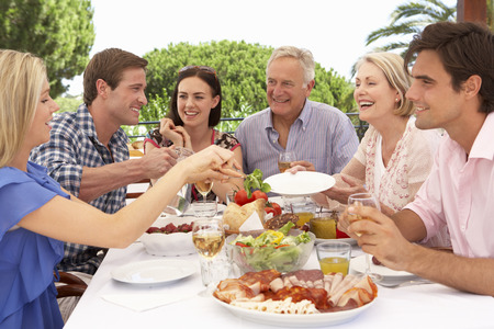 Extended Family Group Enjoying Outdoor Meal Together