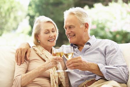 parejas enamoradas: Retrato de los pares mayores que se relajan en el sofá con copa de vino