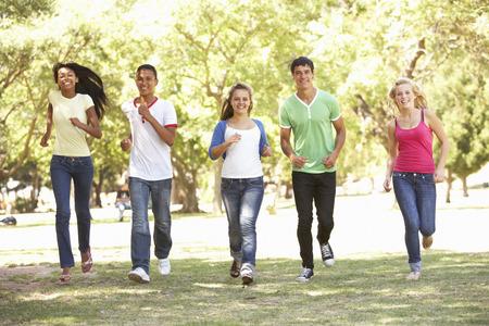 gente corriendo: Grupo de amigos adolescentes que se ejecutan en parque