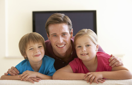 widescreen: Father And Children Watching Widescreen TV At Home Stock Photo