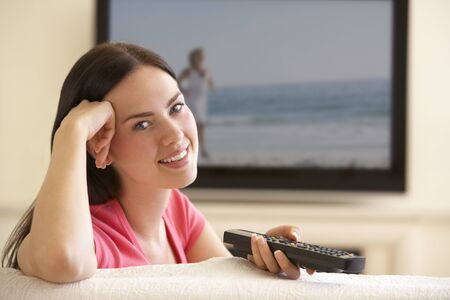widescreen: Woman Watching Widescreen TV At Home Stock Photo