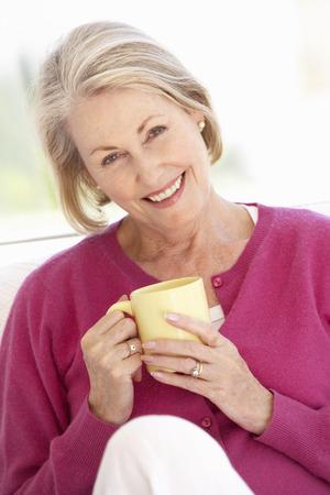 tomando café: Mujer mayor que se relaja en el país con la bebida caliente