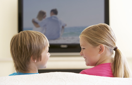widescreen: Two Children Watching Widescreen TV At Home Stock Photo