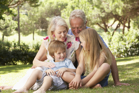 causal clothing: Grandparents And Grandchildren Sitting In Park Together