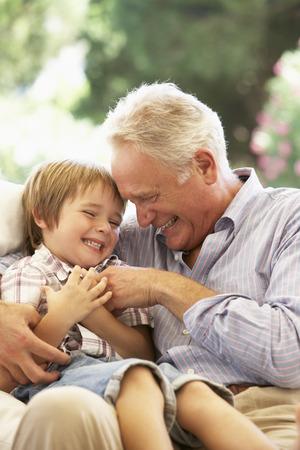 ソファで一緒に笑いながら孫と祖父