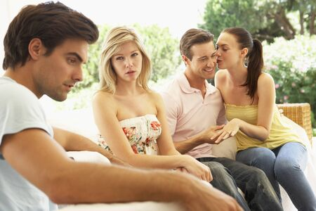 amongst: Couple With Problems Amongst Group Of Friends Relaxing On Sofa Stock Photo