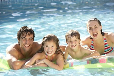 семья: Молодая семья, расслабляющий в бассейне Фото со стока