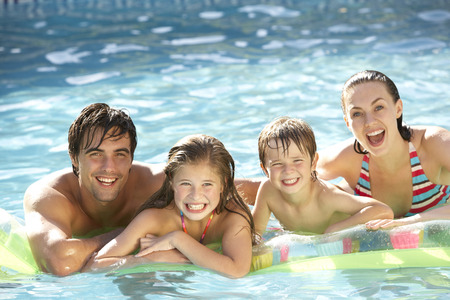 child swimsuit: Young Family Relaxing In Swimming Pool