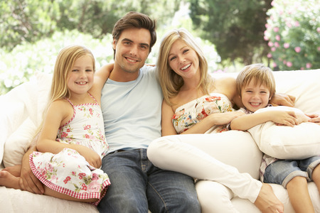 family sofa: Portrait Of Young Family Relaxing On Sofa