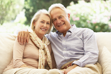 couple relaxing: Portrait Of Senior Couple Relaxing On Sofa