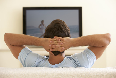 Man Watching Widescreen TV At Home Stock Photo