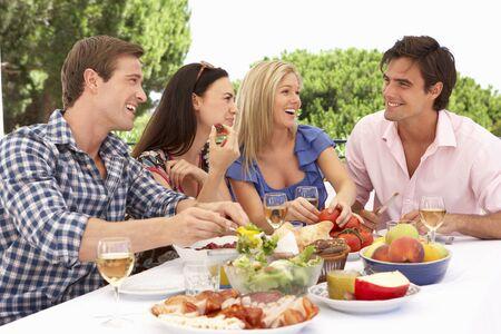 tomando alcohol: Grupo de amigos jovenes que disfrutan de la comida al aire libre Juntos Foto de archivo