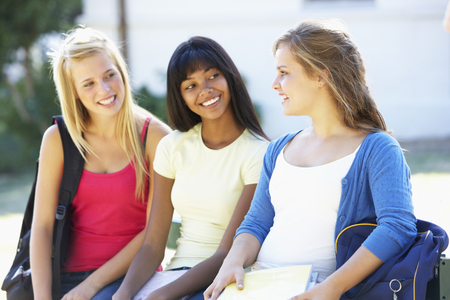 textbooks: Three Female College Students Sitting On Bench With Textbooks Stock Photo