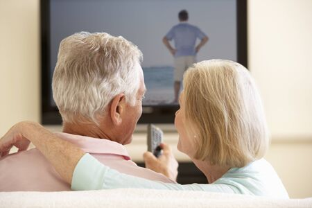 widescreen: Senior Couple Watching Widescreen TV At Home Stock Photo