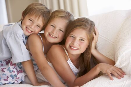 eleven: Group Of Children Relaxing On Sofa At Home Stock Photo