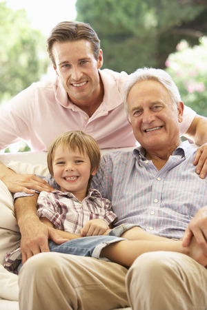 grown ups: Grandfather With Son And Grandson Laughing Together On Sofa Stock Photo
