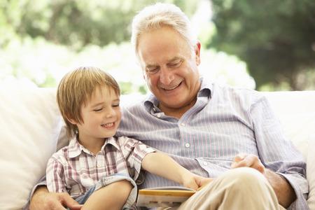 ソファーで一緒に読書を孫と祖父 写真素材