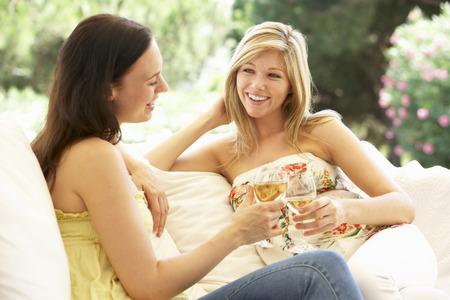 Два женских друзей, расслабляющий на диване с бокалом вина