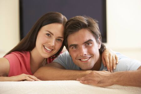 widescreen: Couple Watching Widescreen TV At Home