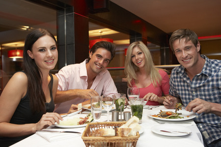 Group Of Young Friends Enjoying Meal In Restaurant