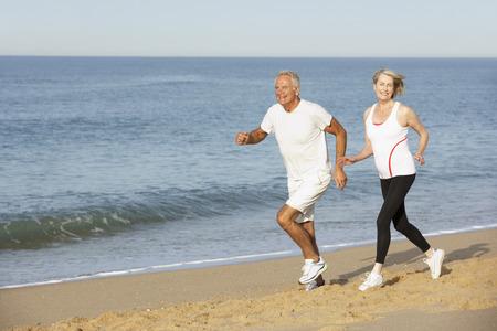 outdoor fitness: Senior Couple Jogging Along Beach
