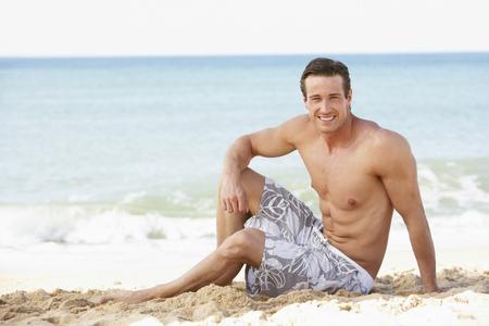 swimming costume: Young Man Wearing Swimming Costume Sitting On Beach