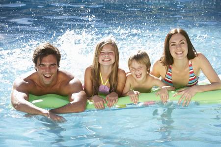 家族一緒にプールでリラックス 写真素材