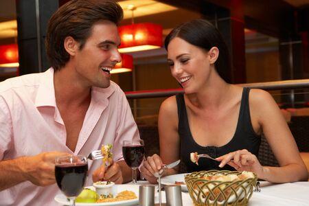 comidas: Pares jovenes que disfrutan de la comida en restaurante
