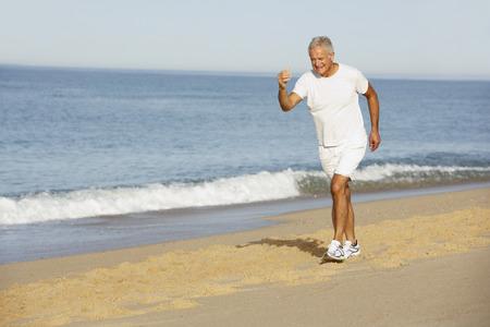 gente corriendo: Hombre mayor que activa largo de la playa